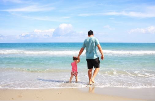 child holding father's hand on beach